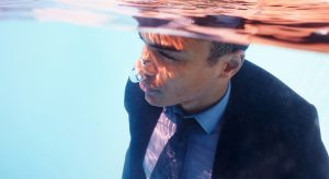 Closeup portrait of business executive drowning under water